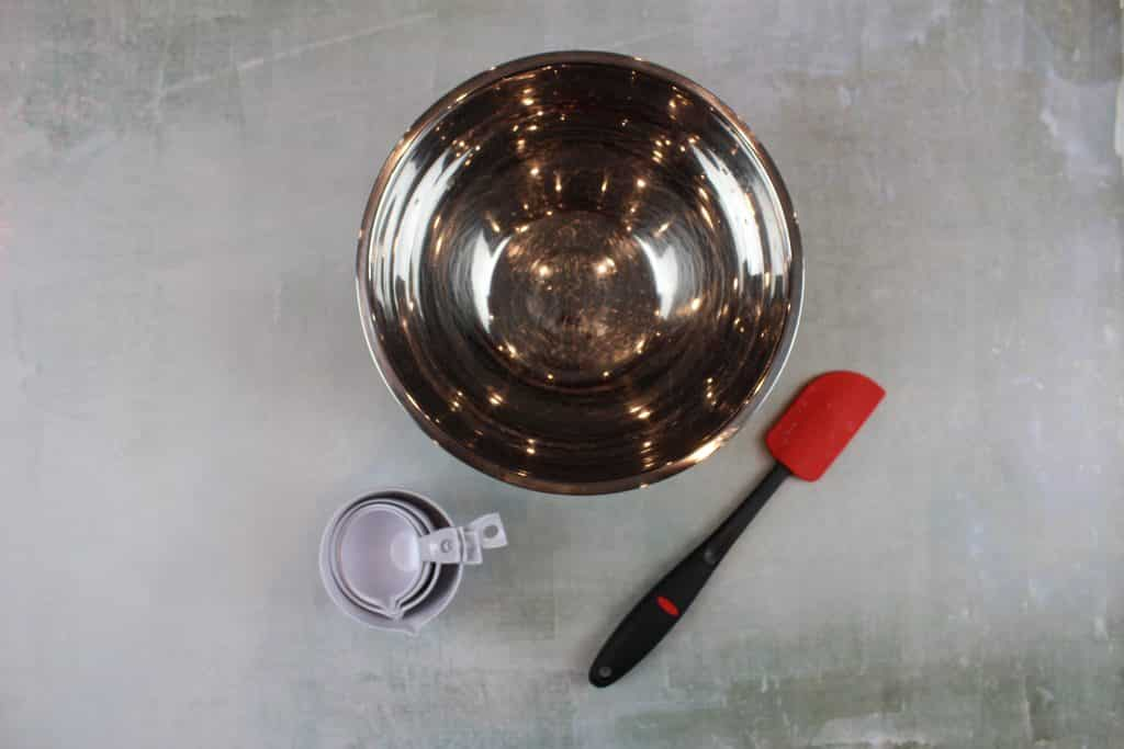 metal mixing bowl, set of white measuring cups and a red spatula on a green background