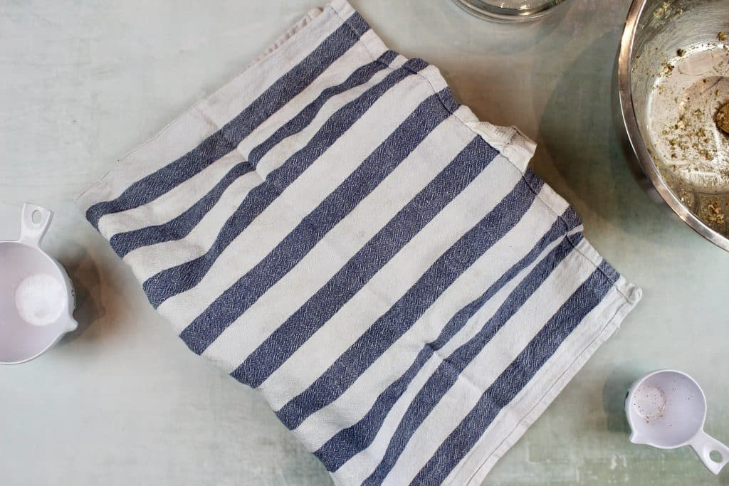 a container covered by a white and blue striped teatowel