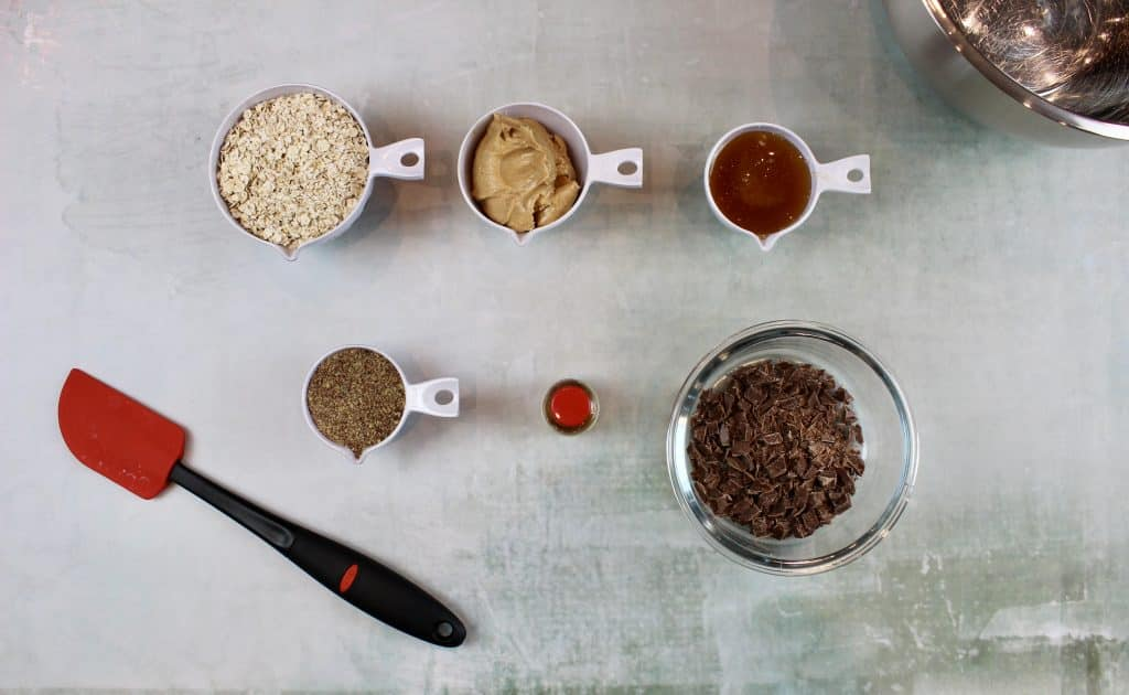 Ingredients for easy no bake energy balls in containers with a red spatula on a green background